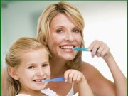 Picture of a mother and daughter brushing their teeth and practicing preventive dentistry.