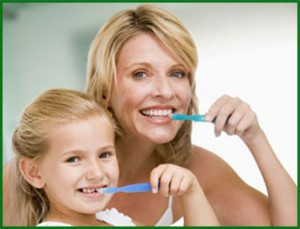 Picture of a mother a daughter brushing and practicing good dental care to prevent periodontal disease.